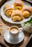 Breakfast in bed with espresso, flower and croissant Royalty Free Stock Image