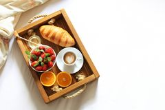 Breakfast in bed tray with cup of coffee, fresh french croissant and fruits on white sheet top view, copy space. Honeymoon. Mornin. Breakfast in bed flat lay royalty free stock image