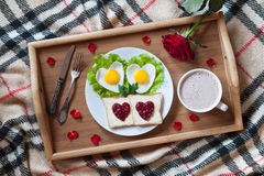 Breakfast in bed with heart-shaped eggs, toasts, jam, coffee, rose and petals. Valentines Day surprise. Stock Images
