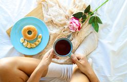 Breakfast in the bed. Homemade. Girl is eating the lunch. stock photos
