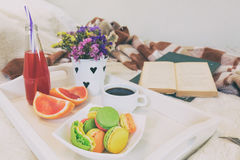 Breakfast in bed with hot coffee and macaroons. Royalty Free Stock Photography