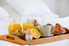 Breakfast in bed in hotel room. Royalty Free Stock Photography