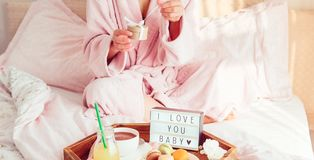 Breakfast in bed with I love you text on lighted box, coffee, macaroons on wooden tray and cropped woman in a bathrobe opening stock photos