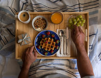 Breakfast in bed. Man having breakfast served in bed on a wooden tray Royalty Free Stock Images