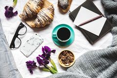 Breakfast in the bed. Morning, croissant, coffee, flowers and a notebook with a pen. Planning stock photography