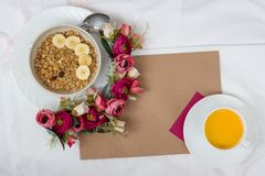 Breakfast in bed with flowers and a card. Breakfast in bed with muesli, fruit and orange juice with flowers and a card royalty free stock images