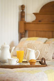 Breakfast in the bed. Breakfast in bed with orange juice and muffin on a tray in a country style environment Royalty Free Stock Images