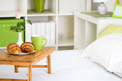 Breakfast in bed with pastries on a tray. And a rose in the vase Royalty Free Stock Photography