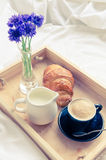 Breakfast in bed. Romantic summer breakfast in bed, tray with fresh croissant, cup of coffee espresso with milk and bouquet of blue cornflowers. Good morning Royalty Free Stock Photos