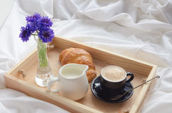 Breakfast in bed. Romantic summer breakfast in bed, tray with fresh croissant, cup of coffee espresso with milk and bouquet of blue cornflowers. Good morning Royalty Free Stock Image