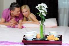 Breakfast in bed. Smiling young couple together getting ready to enjoy breakfast in bed Stock Photos