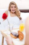 Breakfast in bed. Surprised young woman lying in bed while her boyfriend serving breakfast in bed Stock Image