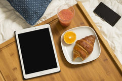 Breakfast at bed with tablet and mobile Royalty Free Stock Photo
