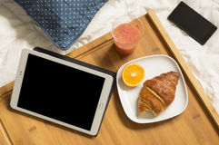 Breakfast at bed with tablet and mobile Royalty Free Stock Photos