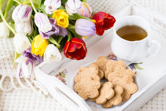 Breakfast in bed. Tea, cookies and flowers Royalty Free Stock Photo