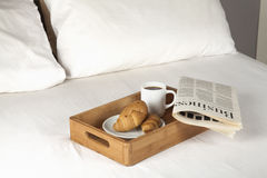 Breakfast on bed. Breakfast tray and newspaper on a bed Stock Images