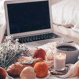 Breakfast in bed, a tray of tea, croissants, fruit, flowers and laptop Morning. Blogger theme. concept of working at home.  stock photos