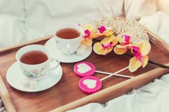 Breakfast in bed in Valentines day. Cup of tea and sweet candies. Love or holiday concept Stock Image