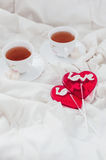 Breakfast in bed in Valentines day. Cup of tea and sweet candies. Love or holiday concept Royalty Free Stock Photo