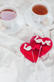 Breakfast in bed in Valentines day. Cup of tea and sweet candies. Love or holiday concept Royalty Free Stock Photos