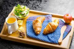 Breakfast in bed on wood tray. Apple, croissant, butter, chocolate and salad Royalty Free Stock Photography