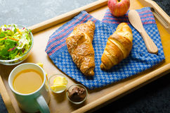 Breakfast in bed on wood tray. Apple, croissant, butter, chocolate and salad Stock Image