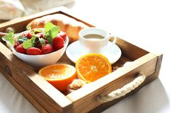 Breakfast in bed, a wooden tray of coffee, croissants, strawberry, orange close up. Honeymoon. Morning at the hotel. Breakfast in bed flat lay. Woman hand Stock Photos