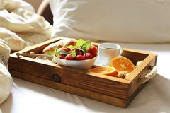 Breakfast in bed, a wooden tray of coffee, croissants, strawberry, orange close up. Honeymoon. Morning at the hotel. Breakfast in bed flat lay. Woman hand Royalty Free Stock Image