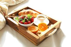 Breakfast in bed, a wooden tray of coffee, croissants, strawberry, orange close up. Honeymoon. Morning at the hotel. Breakfast in bed flat lay. Woman hand Stock Images