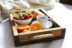 Breakfast in bed, a wooden tray of coffee, croissants, strawberry, orange close up. Honeymoon. Morning at the hotel. Breakfast in bed flat lay. Woman hand Stock Photo