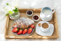 Breakfast in bed. Wooden tray with coffee , jam, strawberries and croissants. Decoration of delicate white flowers. Beautiful sunlight stock photo