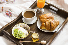 Breakfast in bed in wooden tray with coffee, juice, muesli with Stock Photo