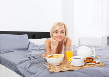 Breakfast in bed, young woman lying on bed Stock Photos