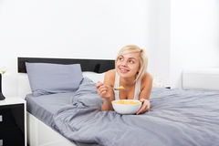 Breakfast in bed, young woman lying on bed Stock Photography