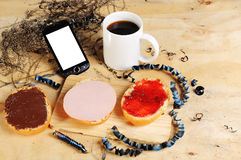 Breakfast on a bench with bread rolls a cup of coffee and mobile phone. Breakfast on a bench with bread rolls a cup of coffee, a mobile phone and metal cuttings Stock Images