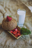 Breakfast of berries with a bun and a glass of milk Stock Photography