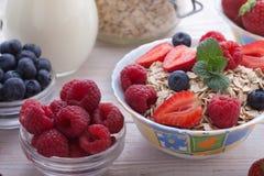 Breakfast - berries, fruit, milk and muesli on white wooden. Summer breakfast. Ingredients for healthy breakfast - berries, fruit, milk and muesli on white Royalty Free Stock Photo