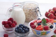 Breakfast - berries, fruit and muesli on white wooden. Berries, fruit, milk and muesli ingredients for healthy breakfast on white wooden table, close-up top view Stock Photo