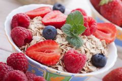 Breakfast - berries, fruit and muesli on white wooden Stock Photo