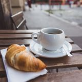 Breakfast with black coffee and croissants on the wooden table in an outdoor cafe. City on a background stock photos