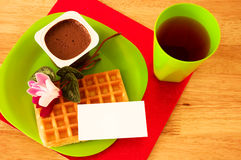 Breakfast with blank ticket. Waffle, chocolate mousse and juice, decorated with flowers and blank ticket placed on plate stock images