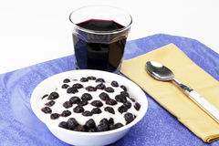 Breakfast in Blue. Glass of organic blueberry juice, frozen blueberries with yogurt in a bowl near a spoon on a placemat Stock Photography