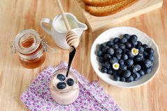 Breakfast with blueberries, honey and yogurt. Breakfast with tea, honey, blueberries and yogurt for healthy lifestyle royalty free stock photo