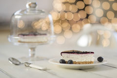 Breakfast. A blueberry cheesecake on a white wooden table, a cloche with more cheesecake and a spoon.  Some bokeh lights in the background stock images