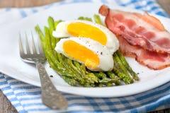 Breakfast:  boiled egg, baked asparagus Stock Photos