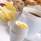Breakfast of boiled egg coffee croissants. And butter over white background Royalty Free Stock Image