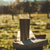 Breakfast with a book in the open air. Steam over a thermo cup. Open book on nature. Book and drinking coffee. Reading at outdoor stock photo
