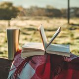 Breakfast with a book in the open air. Steam over a thermo cup. Open book on nature. Book and drinking coffee. Reading at outdoor stock photography