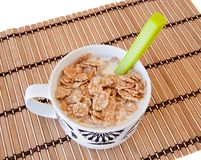 Breakfast bowl of cereal and milk. On bamboo tablecloth royalty free stock image
