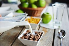 Breakfast with bowl of chocolate cereal and milk Stock Photos